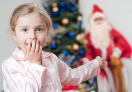 Ребенок думает под елочкой подарки